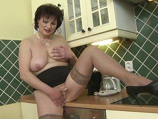 Short haired brunette MILF Dalia masturbates in make an issue of kitchen